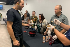 A team member looks ecstatic as he receives toppings for an ice cream sundae at a company event.