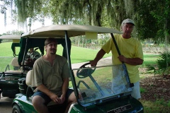 An older image of two team members on a golf outing, posing outside of a golf cart.