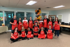 HR team members from PGTI pose for a photo while wearing red aprons for an event.