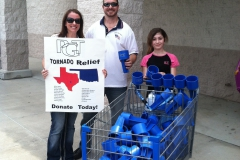 Two adults and a child stand next to a shopping cart and hold up a sign promoting PGT Tornado Relief efforts.
