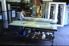 An older image of two team members working with machinery together in a warehouse.