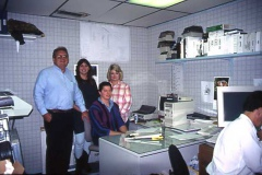 An older image of team members within a small PGTI office.